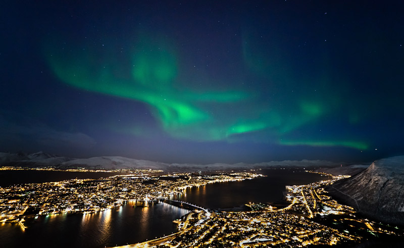 norway tromso northern lights behind city lights