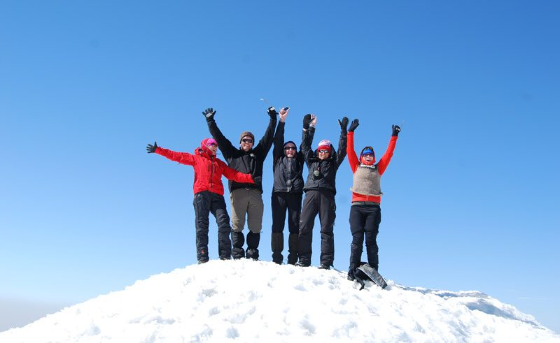east fjords mt snaefell day tour hikers on top of snow capped moutain