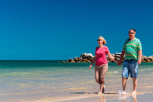 australia couple walking on golden beach istk