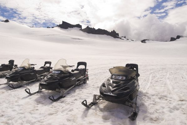 south iceland snowmobiles awaiting drivers on glacier istk