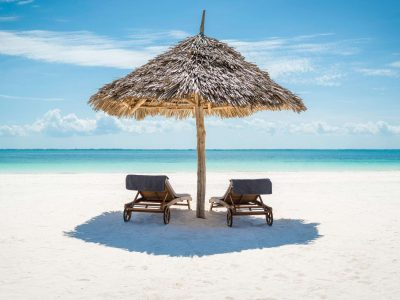 zanzibar wooden loungers and umbrella on beach istk